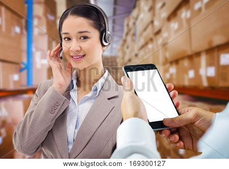 hand holding smartphone against shelves with boxes in warehouse