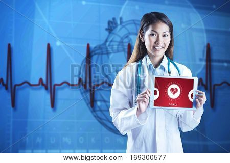 Asian doctor showwing her tablet against blue medical background with heart diagram and ecg