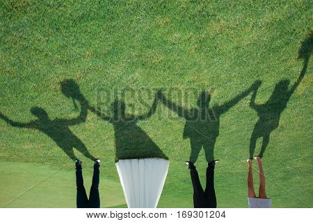 Only shadows of bride groom and guests hold hands and raised them up on a green field
