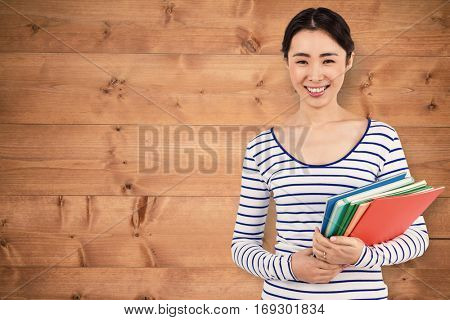 Happy woman holding files against bleached wooden planks background