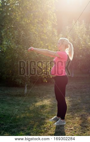 Pregnant woman doing exercises with dumbbells. Expectant female practicing fitness in garden early in morning, sunrise light. Health an body care, healthy pregnancy, sport concept