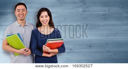 Happy couple holding books against bleached wooden planks background
