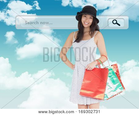 Pretty woman with shopping bags against blue sky