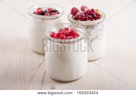 Homemade yogurt with frozen berries red currants black currants raspberries and cranberries in three banks