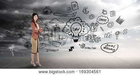 Smiling businesswoman with crossed arms against ominous landscape