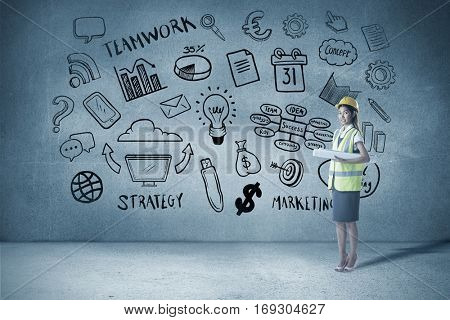 Architect woman with yellow helmet and plans against grey room