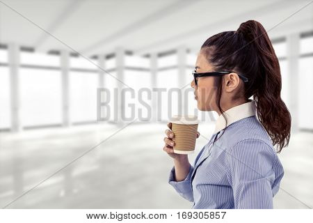 Businesswoman holding disposable cup and looking at wall with notes against view of modern interior