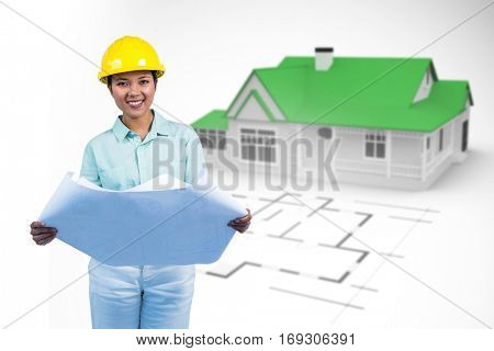 Architect reading a plan with yellow helmet against blue house behind an architectural plan