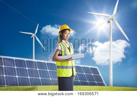 Architect woman with yellow helmet and plans against large solar panel and three wind turbines