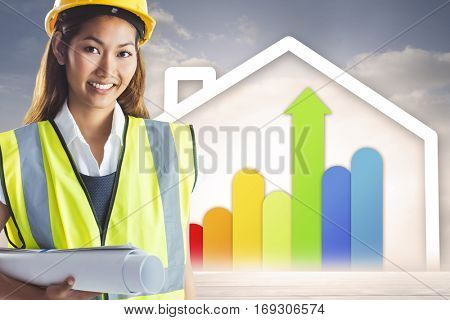 Architect woman with yellow helmet and plans against diagram of a house with energy rating chart
