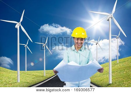 Architect reading a plan with yellow helmet against road leading out to the horizon with wind turbines either side