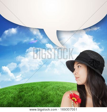 Cheerful woman with flower looking away wearing a hat against green hill under blue sky
