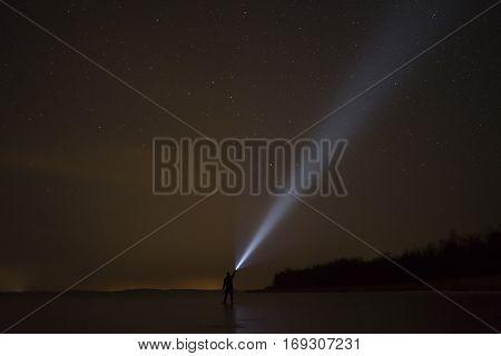 Human shining with flash light at night