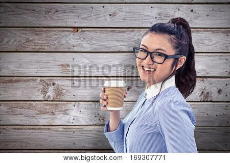 Businesswoman holding disposable cup and looking at wall with notes against digitally generated grey wooden planks