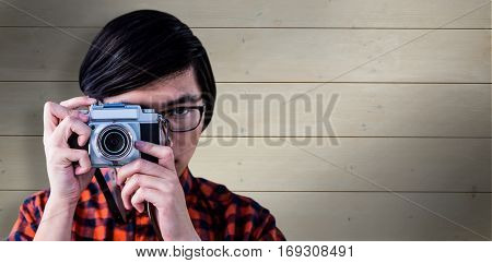 Hipster taking pictures with an old camera against bleached wooden planks background