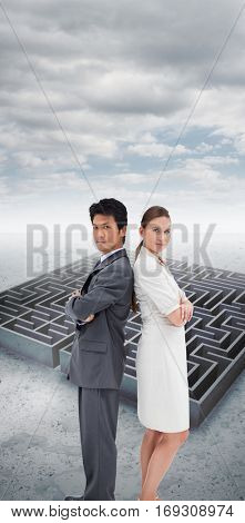 Portrait of business people standing back-to-back against cloudy sky over maze