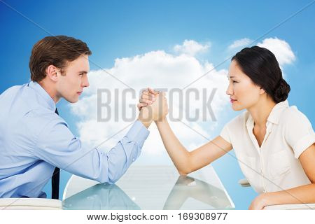 Business couple arm wrestling at desk against cloudy sky