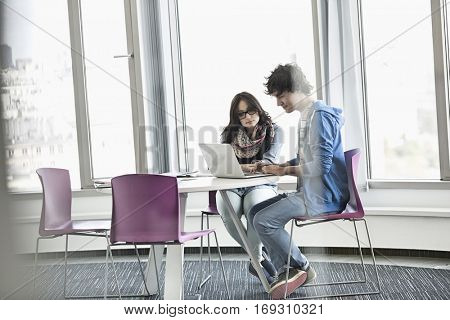 Businesspeople using laptop together in creative office