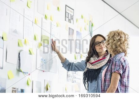 Creative businesswomen discussing over papers stuck on wall in office