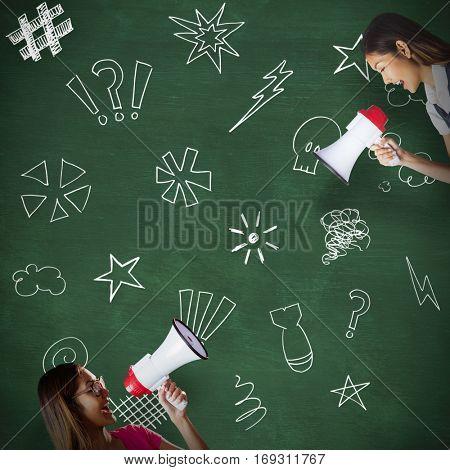 Businesswoman shooting through a megaphone against green chalkboard