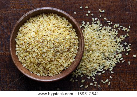 Dry Bulgur Wheat In Brown Wooden Bowl Isolated On Dark Wood From Above. Spilled Bulgur.