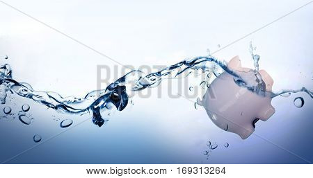 Piggy bank against water bubbling on white surface
