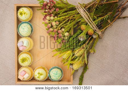 Different cupcakes in a wooden box with a posy of forest flowers