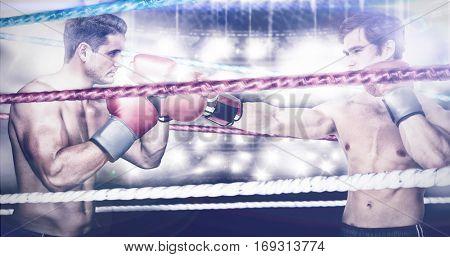 Muscly man wearing red boxing gloves and punching against different cords on black background