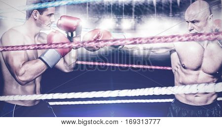 Bald boxer in fighting stance against close up of cords in the boxing ring