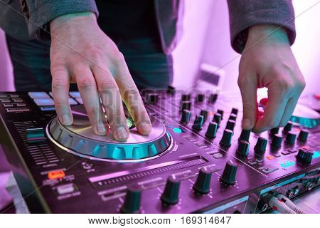 DJ plays and mix music on digital midi mixer controller.