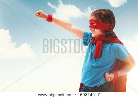 Happy boy in red cape against blue and yellow sky