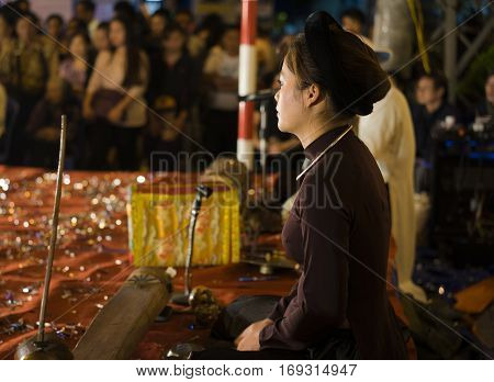Hanoi, Vietnam - Nov 2, 2014: Side portrait of Vietnamese artist perform folk music and song on Ma May st, old town of Hanoi. The show is free for tourist every night