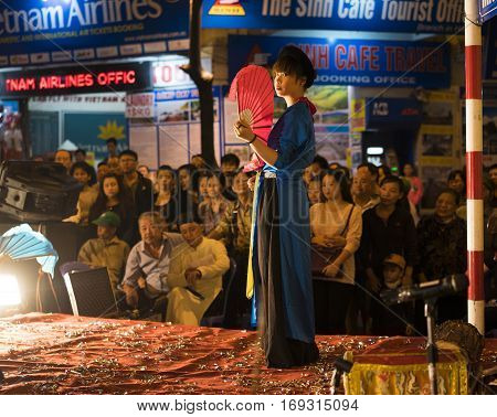 Hanoi, Vietnam - Nov 2, 2014: Dancer with red fan and old traditional clothes performs ancient dance of folk music and song. The show is free for tourist every night in old quarter of Hanoi