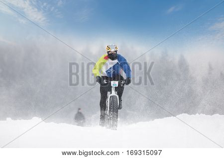 Cyclist in a sports jersey and a mask on his face frost descended winter landscape on a mountain bike on snow sunny day. Sports concept. Adrenaline sport. Winter sports. Destn
