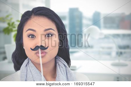Pretty Asian woman with fake mustache posing for camera against documents are posing on the desk