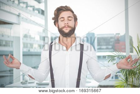 Hipster meditating arms outstretched against working desk in a office