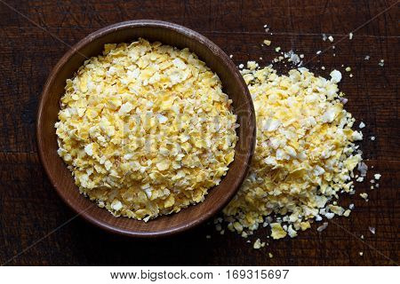 Dry Flaked Corn In Brown Wooden Bowl Isolated On Dark Wood From Above. Spilled Corn.