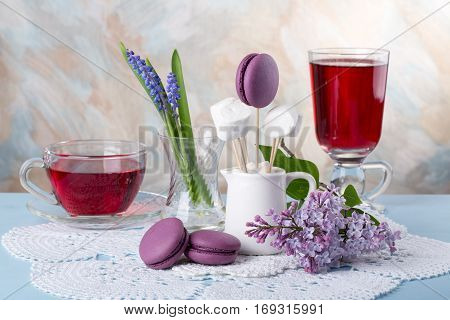Two cup of hibiscus herbal tea lilac flowers and purple French macaroons cookies on the table