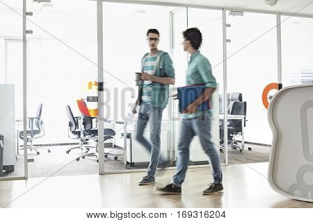 Full-length of businessmen walking at creative work space