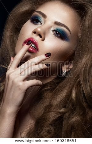 Beautiful girl in Hollywood manner with curls, red lips and blue make-up. Beauty face and hair. Picture taken in the studio