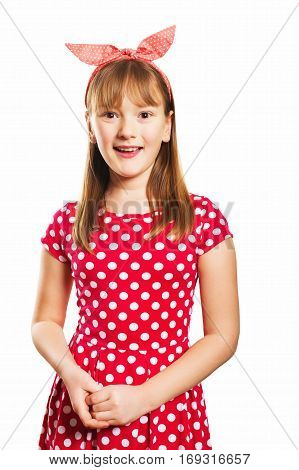 Studio shot of young little 9-10 year old girl, wearing red polka dot dress and headband, isolated on white background, pin up style