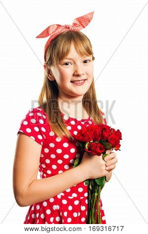 Studio shot of young little 9-10 year old girl, wearing red polka dot dress and headband, isolated on white background, pin up style, holding small bouquet of red roses, mother's day concept