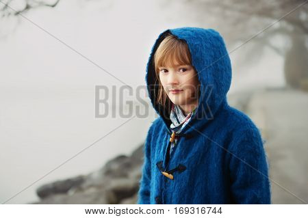 Outdoor portrait of little 9-10 year old little girl on a very foggy day, wearing dark blue coat with hood
