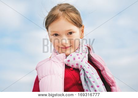 Close up portrait of young 7-8 year old girl against blue sky, wearing pink waistcoat