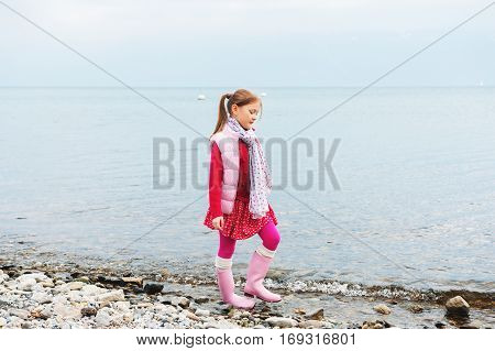 Cute little girl walking by the lake on a cold cloudy day, wearing pink waistcoat and rain boots