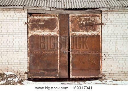 Brick wall of old warehouse with rusty metal door