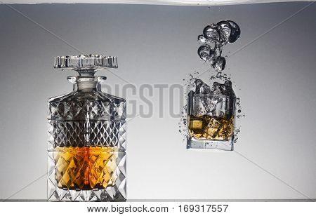 Decanter and glass of whiskey under water