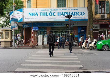 Hanoi, Vietnam - Nov 16, 2014: Perspective of Pharmacy front view and people crossing street on Hang Khay street, near Hoan Kiem lake, center of Hanoi