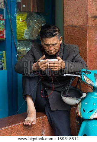 Hanoi, Vietnam - Nov 16, 2014: Senior man reads news and listens to music by earphone from a smartphone on sidewalk on Hang Khay street. Technology development is changing rapidly in Vietnam