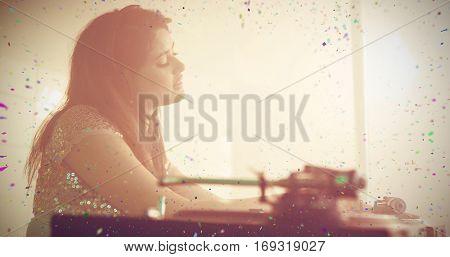 Pretty female DJ playing music against flying colours Pretty female DJ playing music at the nightclub